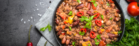Chili con carne in a cast iron pan on dark stone table. Traditional mexican cuisine. Long banner format.