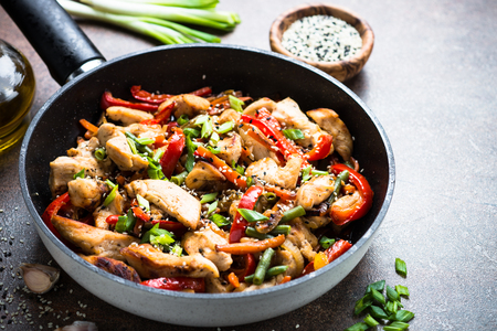 Chicken stir fry with   vegetables and sesame in the wok. Traditional asian food.