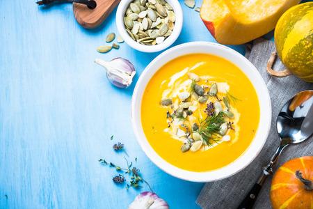 かぼちゃとにんじんのクリーム スープ種子と青いテーブルの上のボウルにハーブ。コピー スペース平面図です。伝統的な秋の味覚。