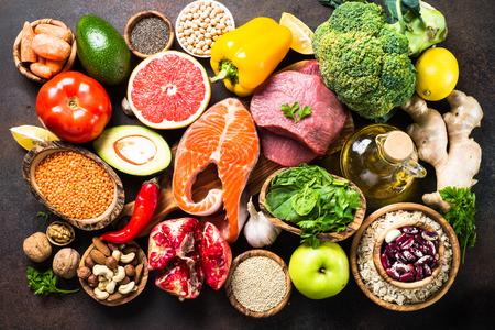 Arrière-plan alimentaire équilibré. Aliments biologiques pour une alimentation saine, superaliments. Viande, poisson, légumineuses, noix, graines, légumes verts, huile et légumes. Vue de dessus sur la table en pierre sombre.
