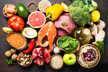 Balanced diet food background. Organic food for healthy nutrition, superfoods. Meat, fish, legumes, nuts, seeds, greens, oil and vegetables. Top view on dark stone table.
