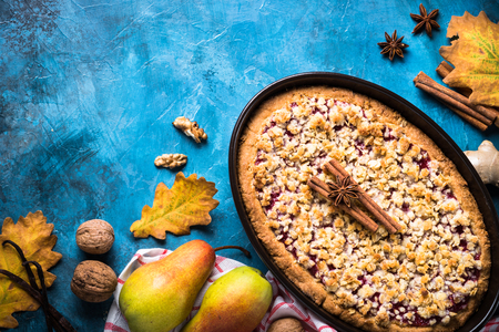 Autumn pie crumble with fruit, ginger and spices on blue table. Top view with copy space. Stock Photo