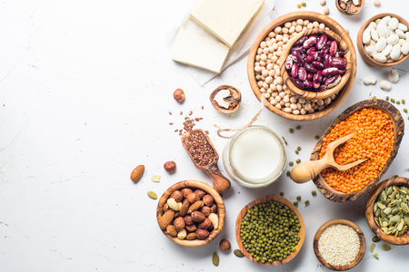 Vegan protein source. Lentils, chickpeas, beans, green mung bean. tofu, vegan milk, seeds and nuts on white background. Top view.