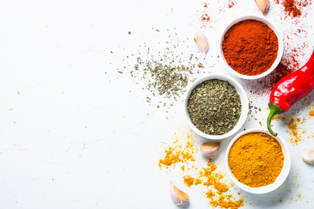 Various spices in a bowls on white background. Top view.