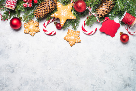 Christmas background. Christmas gingerbread, snow fir tree, red balls and decorations on gray stone background. Top view with copy space. Stock Photo