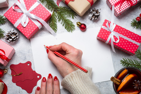 Christmas background. Woman packing Christmas present box and write wishes. Top view.