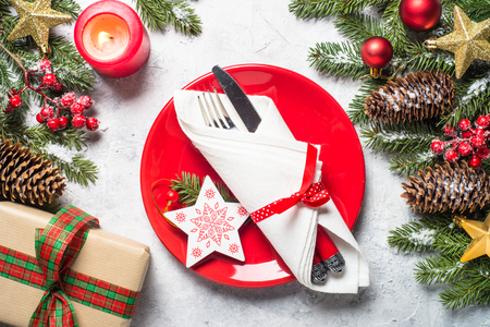 Christmas table setting  with plate, silverware and decorations over gray stone table. Top view. Stockfoto