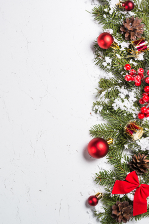 Christmas background. Red christmas decorations with snow fir tree branch on white marble table. Top view vertical.