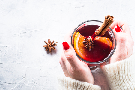 Woman hold Mulled wine in glass mug with spices. Christmas hot drink. Stock Photo