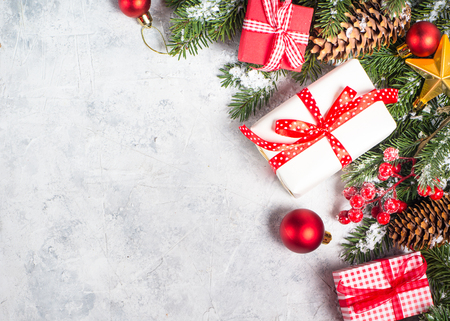 Christmas background. Red christmas present box, fir tree branch and decorations on gray stone table. Top view with copy space. Stock Photo