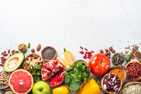 Superfoods on white background. Organic food and healthy vegan food. Legumes,  nuts, seeds, greens, oil and vegetables. Top view with copy space. Stock Photo