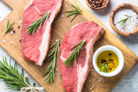 Raw beef striploin steak. Fresh meat ready to cooking. Top view copy space close up. Stock Photo