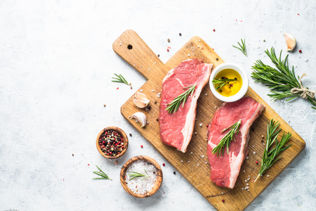 Raw beef striploin steak. Fresh meat ready to cooking. Top view copy space light background.