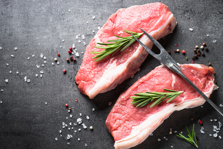 Raw beef striploin steak. Fresh meat ready to cooking. Top view with copy space on black stone background. Stock Photo