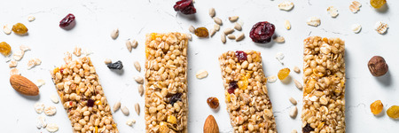 Granola bar. Healthy sweet dessert snack. Cereal granola bar with nuts, fruit and berries on a white stone table. Long banner format. 스톡 콘텐츠