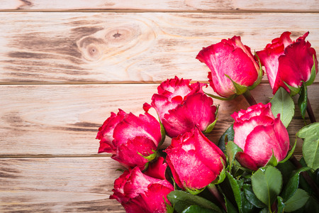 Red rose flower on wooden table.