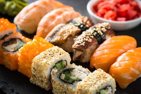 Sushi and sushi roll set on black stone table.