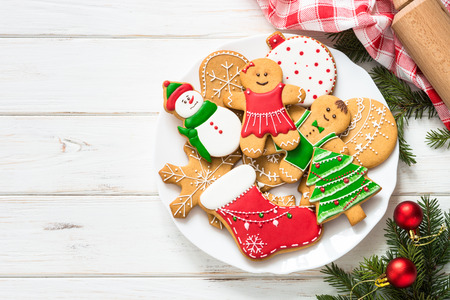Christmas gingerbread on white wooden background. Christmas cooking baking background. Top view with copy space.