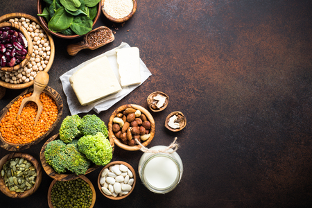Vegan protein source. Tofu, vegan milk, beans, lentils, nuts, broccoli, spinach and seeds. Top view with copy space on dark stone table. Healthy vegetarian food. Stock Photo