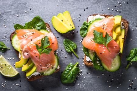 オープンサンドイッチまたはトースト。サーモン、ホワイトチーズ、アボカド、キュウリ、ほうれん草の穀物パン。健康的なスナック、健康的な脂