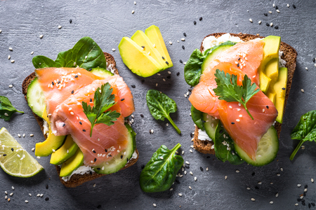 Open sandwich or toast. Grain bread with salmon, white cheese, avocado, cucumber and spinach. Healthy snack, healthy fat and omega 3 source. Top view. Close up.