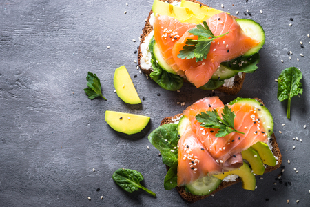Open sandwich or toast. Grain bread with salmon, white cheese, avocado, cucumber and spinach. Healthy snack, healthy fat and omega 3 source. Top view. Close up. Banque d'images - 97609574