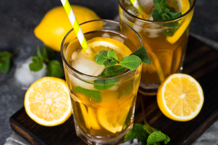 Iced tea. Summer cold drink with black tea, lemon, mint and ice. Stock Photo