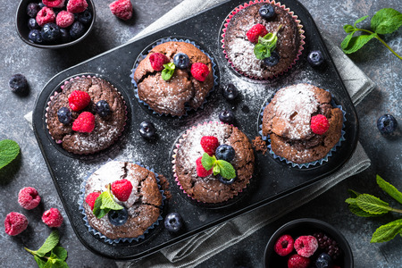 Chocolate orange muffins or cupcakes decorated with fresh berries. Healthy homemade baking. Top view.