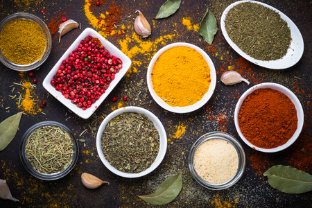 Various spices in a bowls on stone table. Top view.