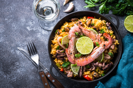 Seafood paella. Traditional spanish dish, european cuisine. Top view on dark stone table. Фото со стока