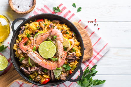 Seafood paella. Traditional spanish dish, european cuisine. Top view on white wooden table.