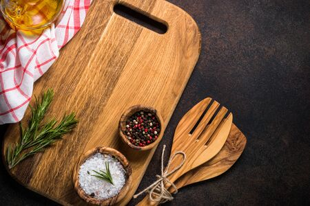 Food background with cooking utensils, cutting board, spices, herbs and olive oil on dark rusty stone table. Top view with copy space.
