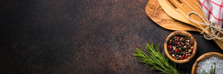 Food background with cooking utensils, cutting board, spices and herbs  on dark rusty stone table. Long banner format. Archivio Fotografico