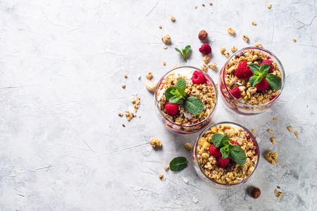 Yogurt parfafait with granola, jam and raspberries on stone table. Healthy dessert top view with copy space.