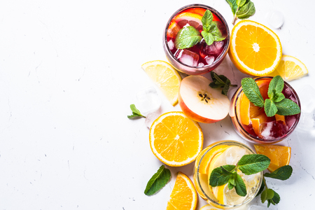White, pink and red sangria with fruit, ice and mint top view. Stock Photo