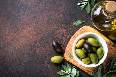 Olives and olive oil on dark stone table top view.