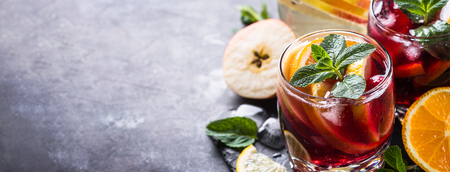 Sangria with fruit, ice and mint in glass. Summer alcohol drink and ingredients. Long banner format.