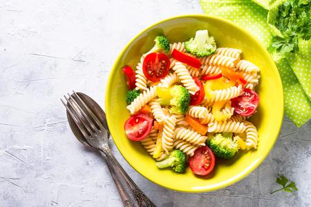 Vegan pasta fusilli with vegetables on white.