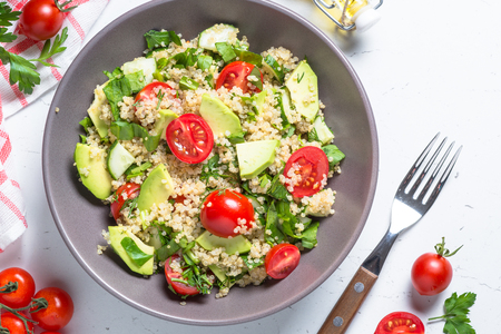 Quinoa salad with spinach, avocado and tomatoes top view. 版權商用圖片