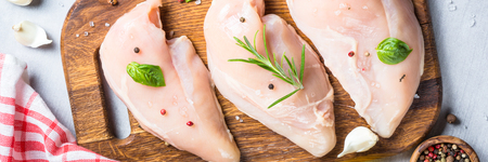 Raw chicken fillet with spices and herbs top view.