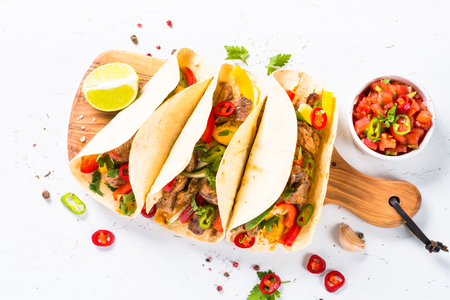 Mexican pork tacos with vegetables and salsa on white. Stock Photo