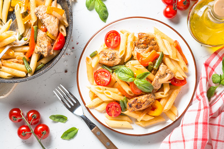 Pasta penne with chiken meat and vegetables. Top view on white background. 免版税图像