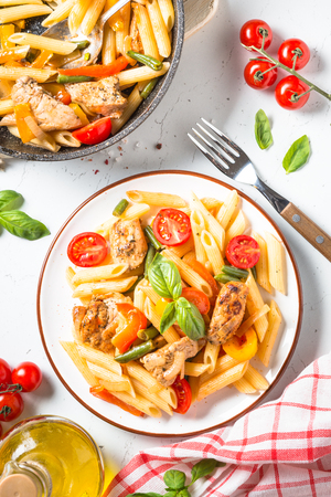 Pasta penne with chiken meat and vegetables. Top view on white background. 写真素材