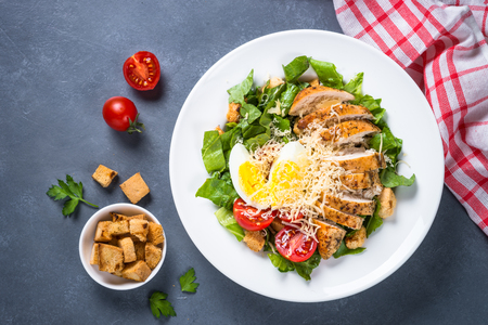 Caesar salad with chicken breast and tomatoes. Top view with copy space. Imagens
