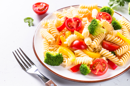 Vegan pasta fusilli with vegetables broccoli and tomatoes.