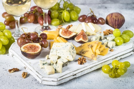 Cheese plate with grapes, figs and nuts. Wine snaks. Cheese assortment. Stok Fotoğraf