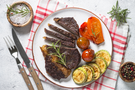 Grilled beef steak with vegetables top view. Stock Photo