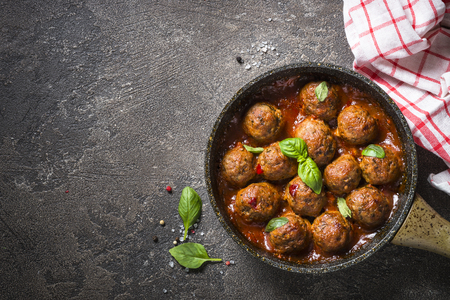 Gehaktballetjes in tomatensaus in een koekenpan op donkere stenen tafel. Stockfoto
