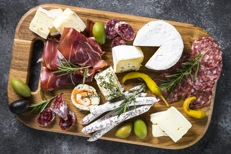 Antipasto board with sliced meat, ham, salami, cheese, olives.