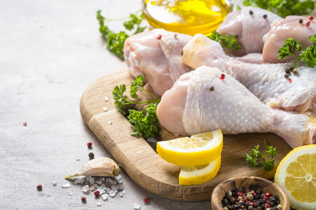 Raw Chicken drumsticks on cutting board with ingredients for cooking.